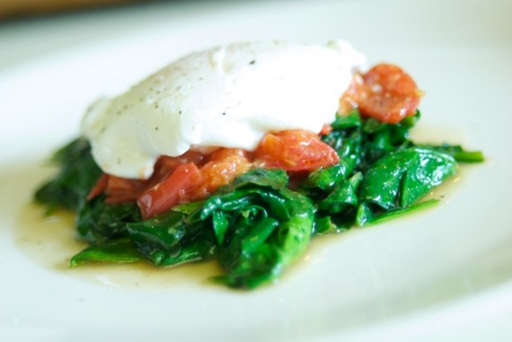 Poached eggs on a bed of spinach and tomatoes